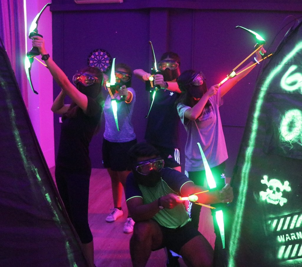 4 people posting with lit up archery