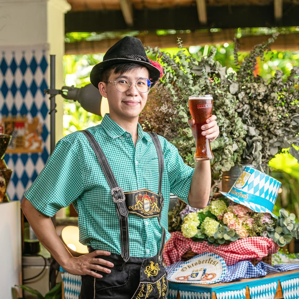 a person holding a glass of beer for Oktoberfest celebration