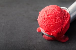 Cherry, raspberry, strawberry, cranberry , red sorbet,scoop, black stone background.