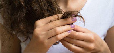 closeup woman hand holding hair split ends purple nail polish malabsorption and hair loss viviscal hair blog