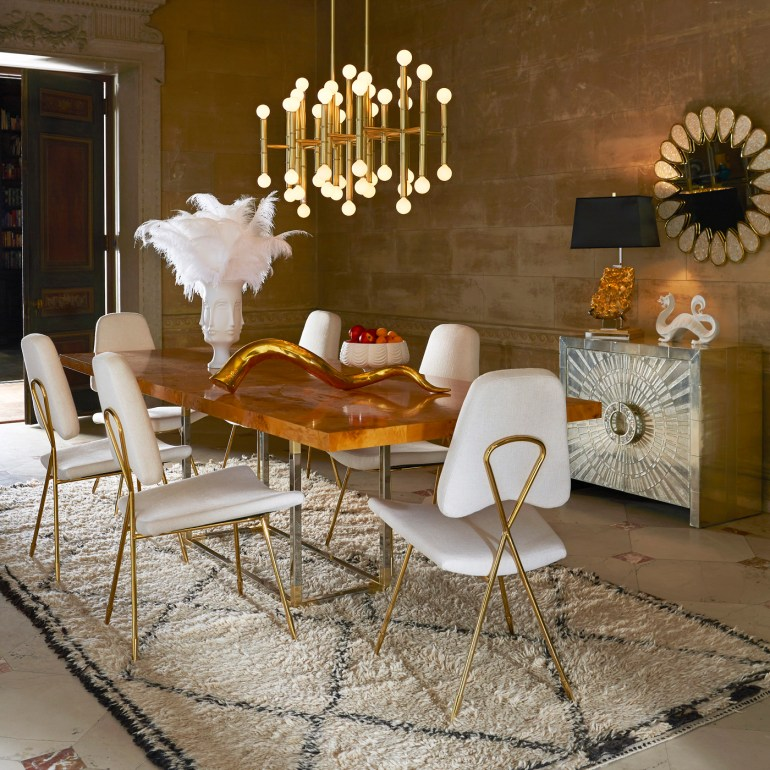 Enchanting Adler-designed diningroom with the minimalist and sculptural brass Maxime Dining Chairs and the Meurice Chandelier