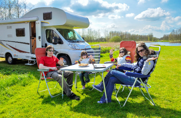 family enjoying a picnic beside their campervan