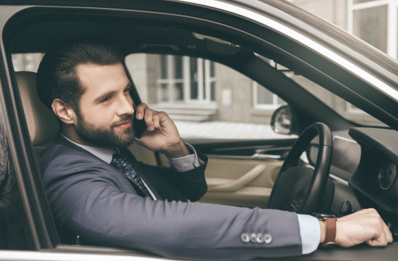 businessman using his phone inside a rental car