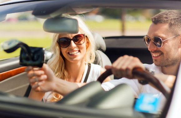 cheerful couple checking GPS while on a road trip