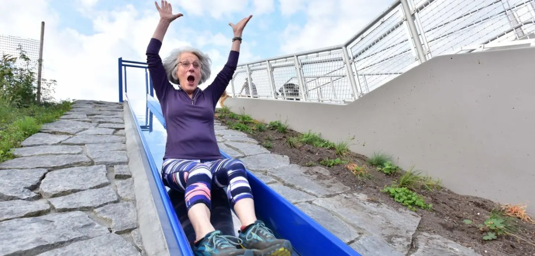 A woman rides a slide from the Wilson Way bridge down to Dune Peninsula at Point Defiance Park in Tacoma