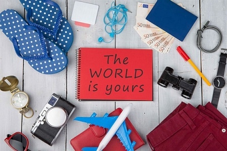"Christmas adventure props - plane, passport, money, camera, compass, note pad with text ""The World is yours"", binoculars, jeans, watch, flip flops, wallet on white wooden table"