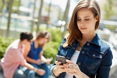 A young lady using her phone to check-in online