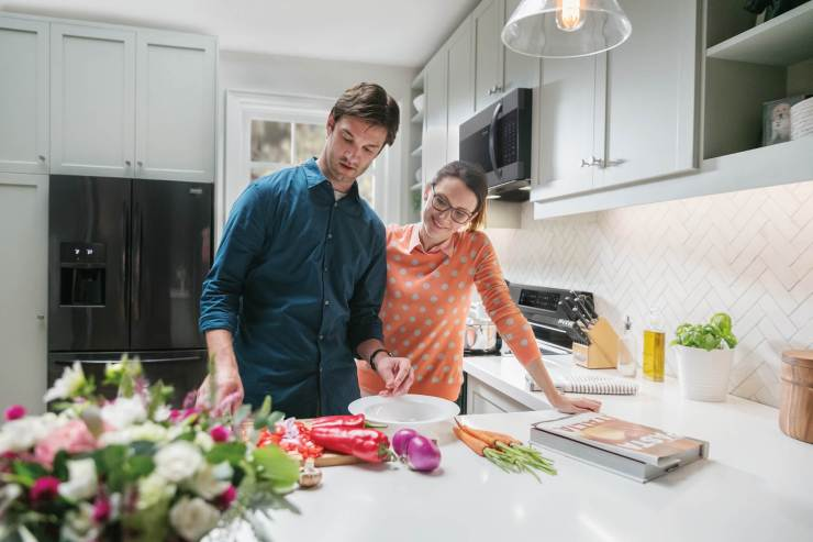 Couple cooking dinner together in kitchen with black Frigidaire appliances