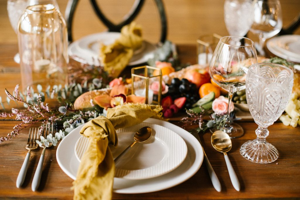 The Grazing Fox Wedding Caterers, image of dining table set up with four utensils, two of each type (spoon and fork). They are gold in appearence, a gold pentagon candle holder sits in the center, next to a platter of fruits, herbs, some flowers and an empty glass vase. To the right of the image, is two glass cups, in the center, there lay two white porcelain plates stacked upon each other, along with a golden desert spoon and a yellow handkerchief. Photo is warm in appearance, across the table sits the exact items in reflection for another placeholder.