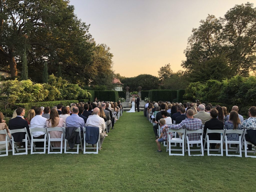 Couple stands in center as outdoor wedding takes place at the Dallas Arboretum and Botanical Gardens Wedding Venue