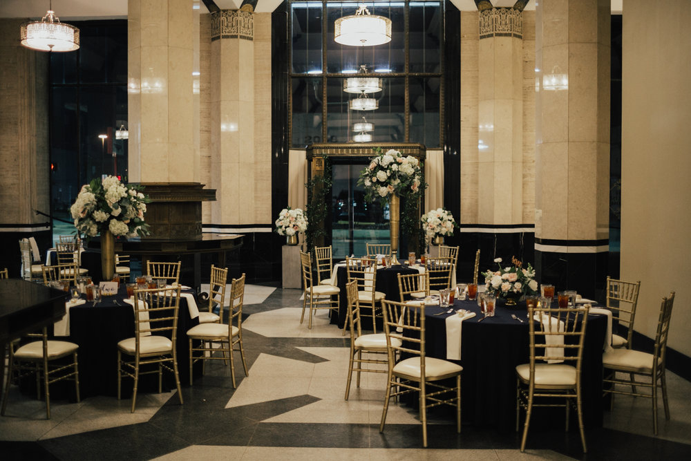 Interior of Carlisle Room, Dallas Wedding Venue. Black and white floor, giant floral centerpieces, white and gold chairs.