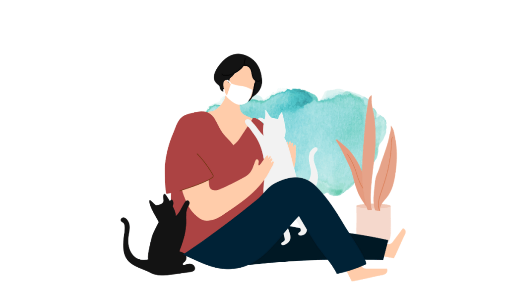 lady wearing a face mask and two cats