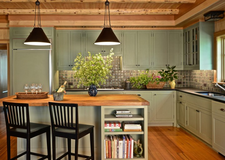 "The kitchen cabinetry in this lakeside home is painted in Farrow & Ball's ""Lichen"" and the pendant lights are by Paul Ferrante"
