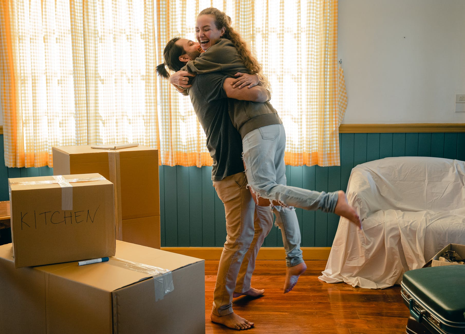 cheerful couple hugging and unpacking carton boxes