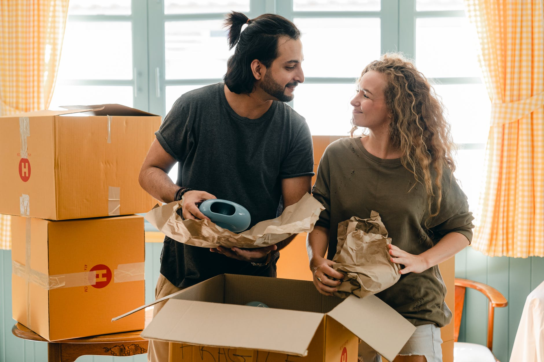 multiethnic couple packing ceramic belongings in parchment before relocation