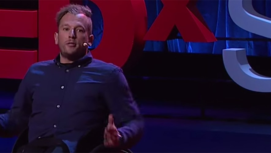 Dylan Alcott is on stage as he speaks to an audience sitting in his wheelchair in front of a Tedx sign