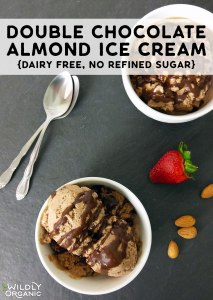 Top down photo of two bowls of double chocolate almond ice cream, two spoons, almonds, and a strawberry.