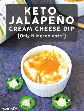A ramekin of keto jalapeño cream cheese dip topped with shredded cheddar cheese and slices of jalapeño.