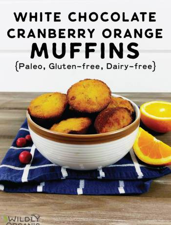 A bowl with paleo white chocolate cranberry orange muffins in them with fresh cranberries and orange slices.