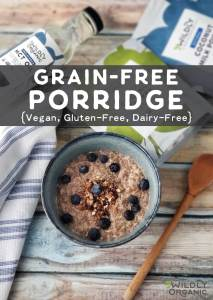 A bowl of grain-free porridge topped with fresh blueberries and Wildly Organic MCT Oil with a spoon.