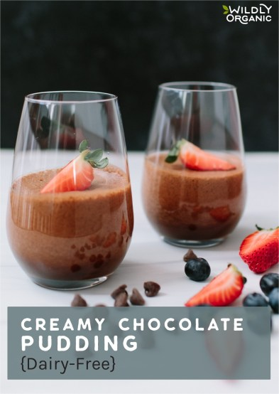 Chocolate pudding in a clear glass with sliced strawberries on top with mixed fruit in the foreground