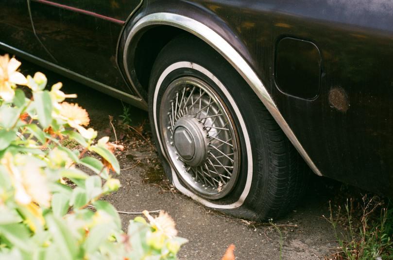 un pneu de voiture à plat, qui est sûrement crevé