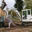 Der zweite Schrankenbock wird mit vollem Einsatz in die vorbereitete Baugrube eingehoben.