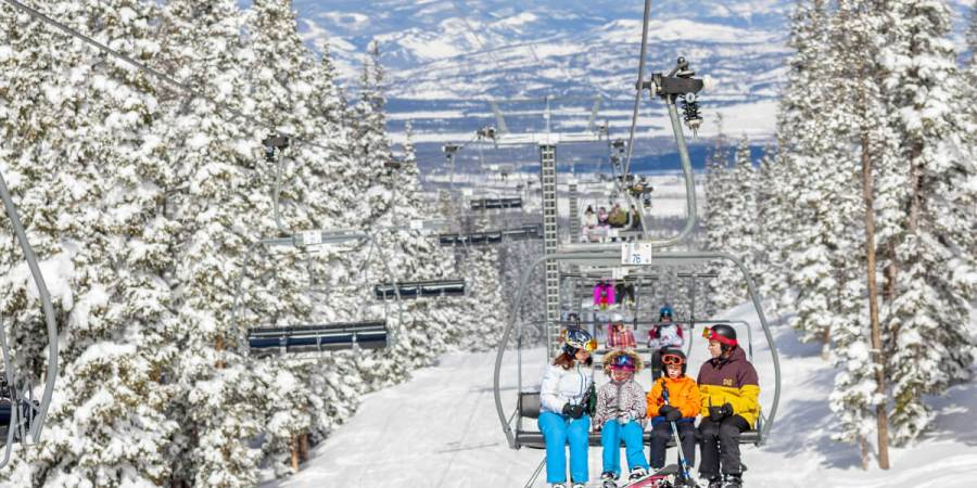 Family sits on a chair lift at Winter Park Resort