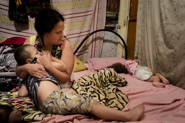 Eliane Stefani holds her 3-year-old son, Eduardo, while Jade, 2, sleeps. (c) Gustavo Basso/WITNESS