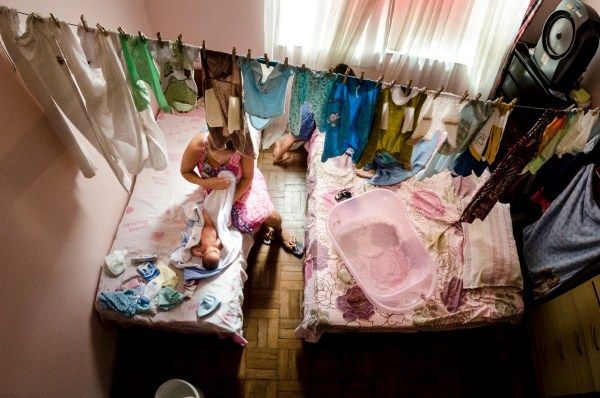 Vera dos Santos' niece bathes her newborn son at her aunt's house. (c) Gustavo Basso/WITNESS