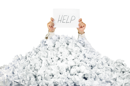 Person under crumpled pile of papers with a help sign