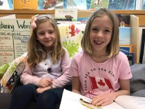 SKY Apple Class student with her Grade 3 reading buddy