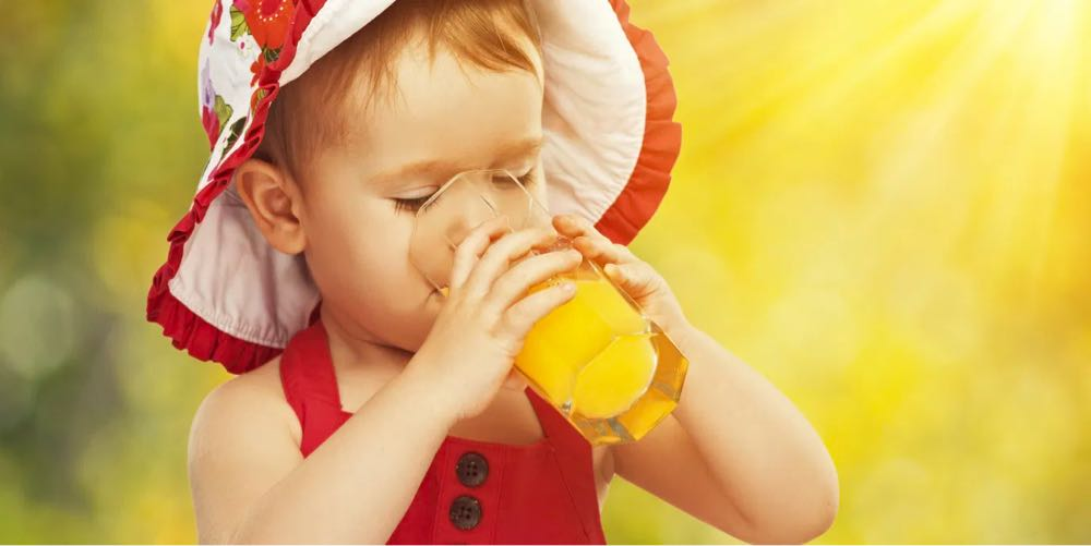 Baby drinking orange juice