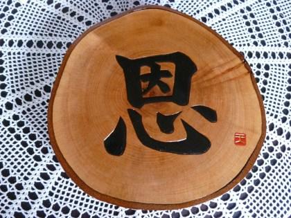 丸太の輪切り板に彫られた「恩」という文字