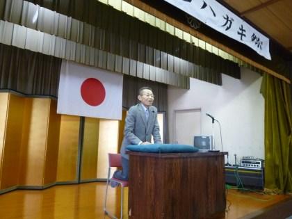 何と演台に座布団を敷き話す坂田道信さん