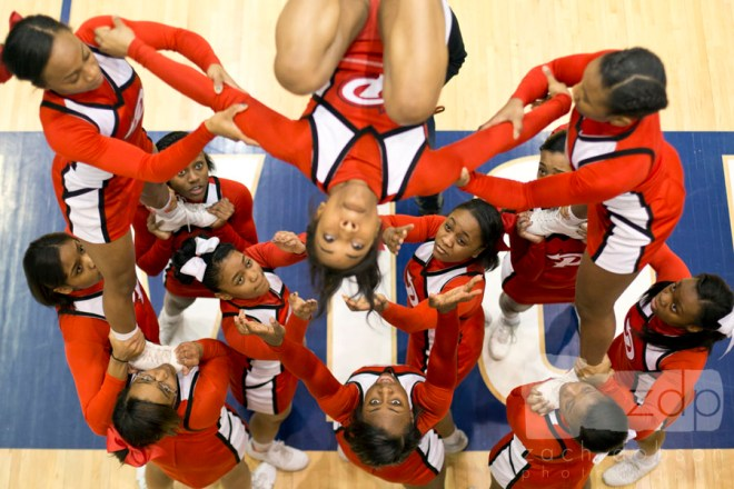 Cheerleaders warm up at the edge of the court before a game. This gym had a raised track that offered this great angle.