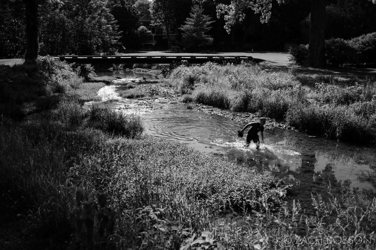 kid walking through a creek