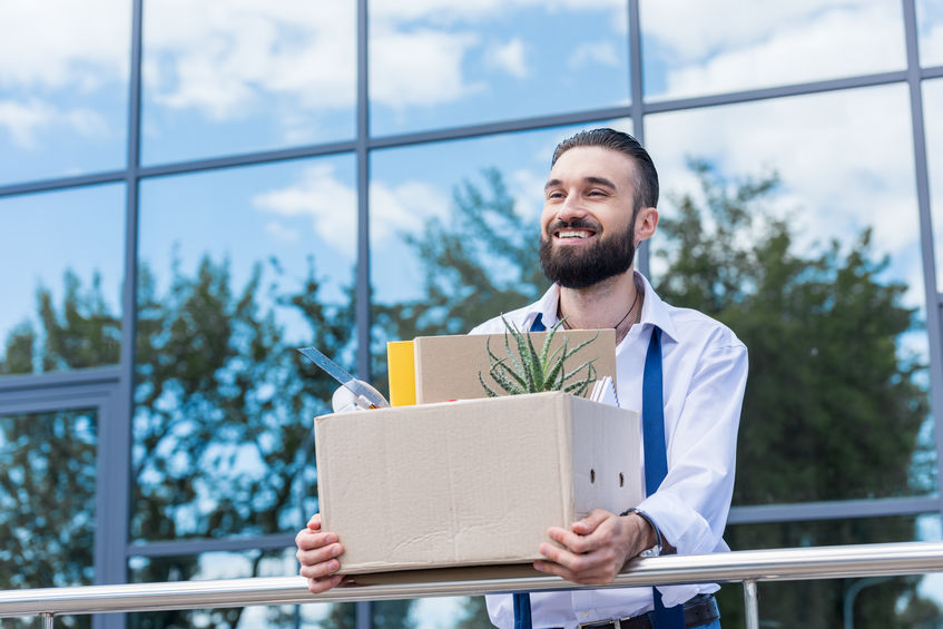 businessman with cardboard box with office supplies in hands standing outside office building, quitting job concept