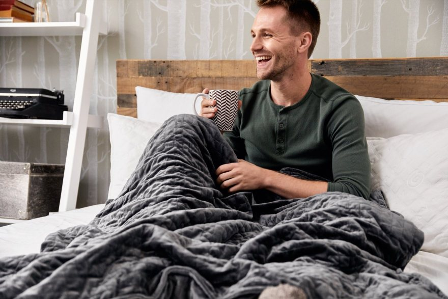 man waking from a good night sleep with weighted blanket