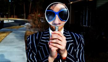 a man wearing a striped suit and holding a magnifying glass up to his face