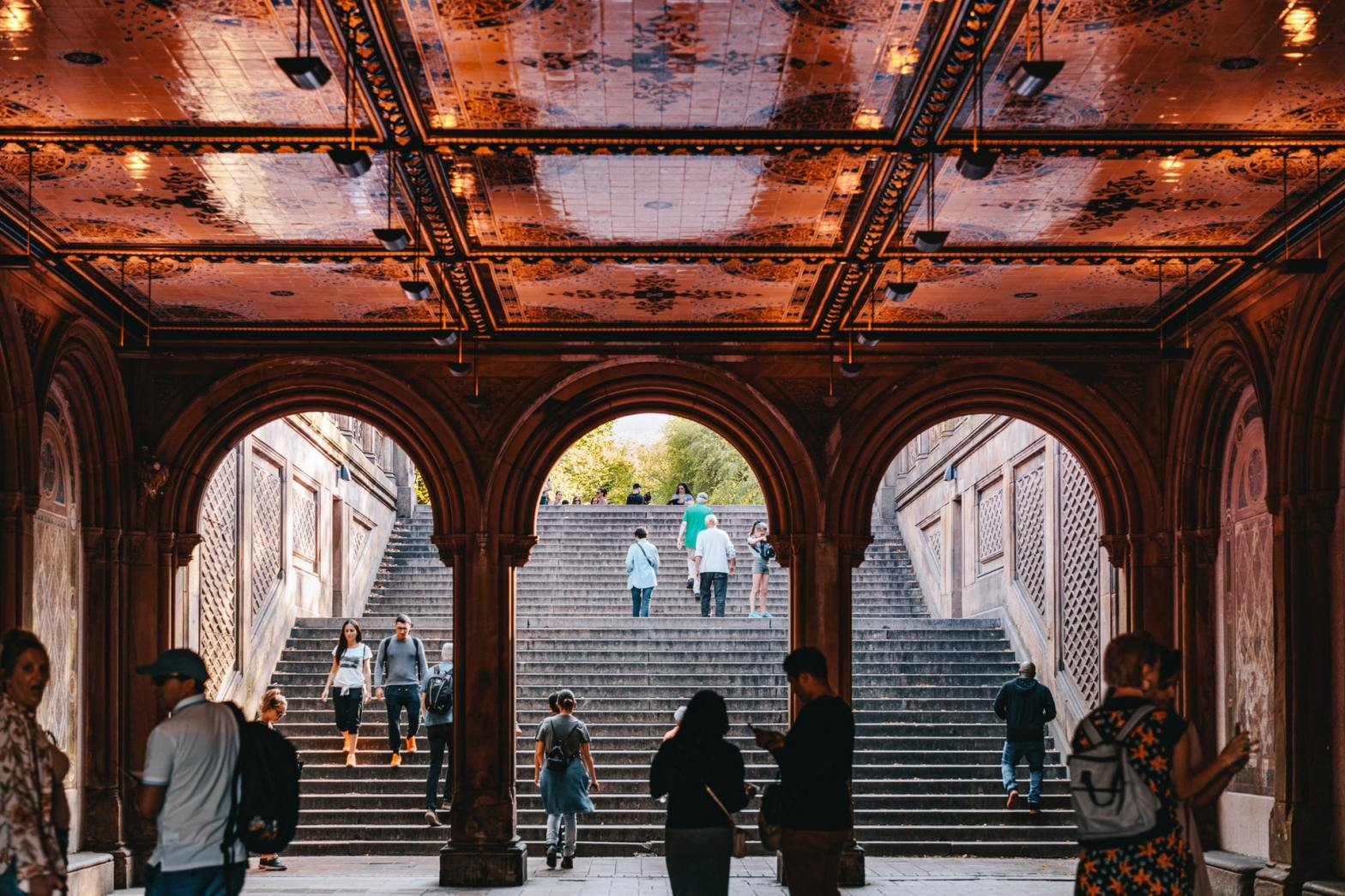 Tourists walking around in Bethesda Terrace in NYC