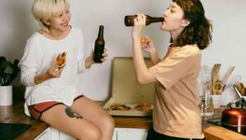Two girls drinking beer and eating pizza