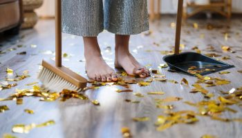 A woman cleaning up confetti off the floor with a broom and a dust pan