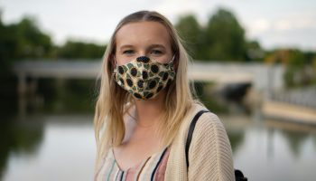 A woman wearing a floral breathable mask which is also a good maskne tip for people with sensitive skin