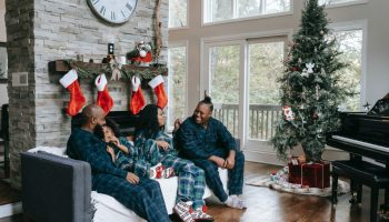 A family sitting on the sofa celebrating Christmas morning together