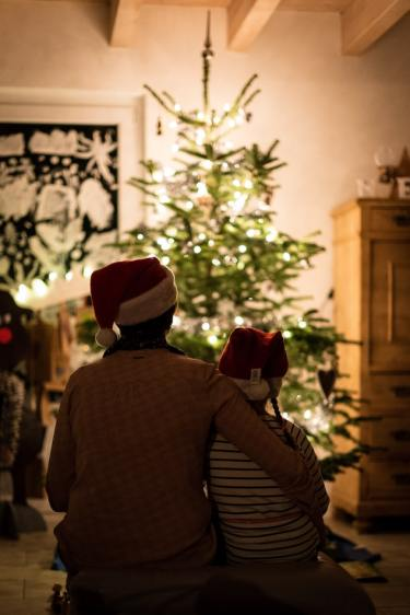 Two people sitting in front of the Christmas tree