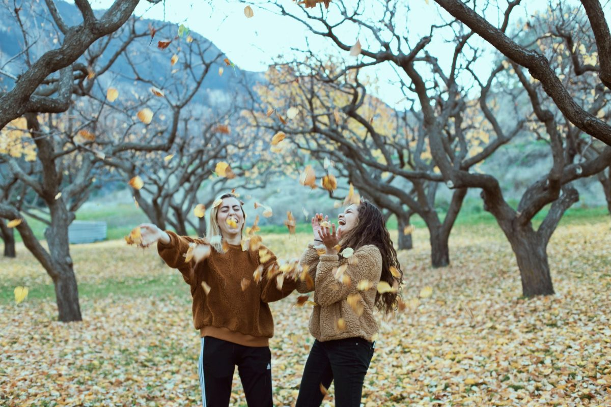 Two girls in a park, throwing leaves up in the air and laughing