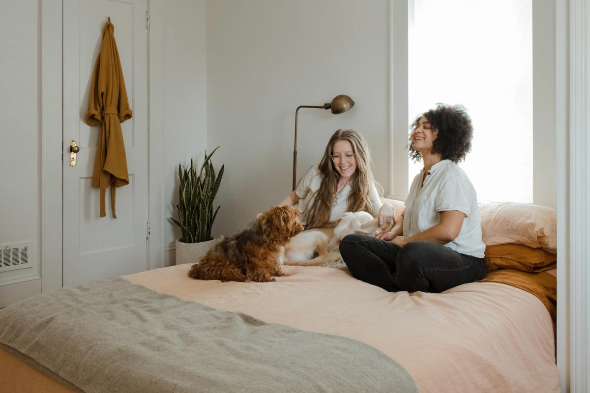 Two women sitting in bed with their pet dog