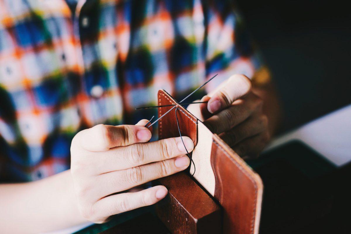 a man stiching a wallet