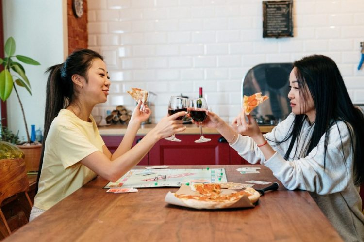 2 girl roommates having pizza and drinking wine